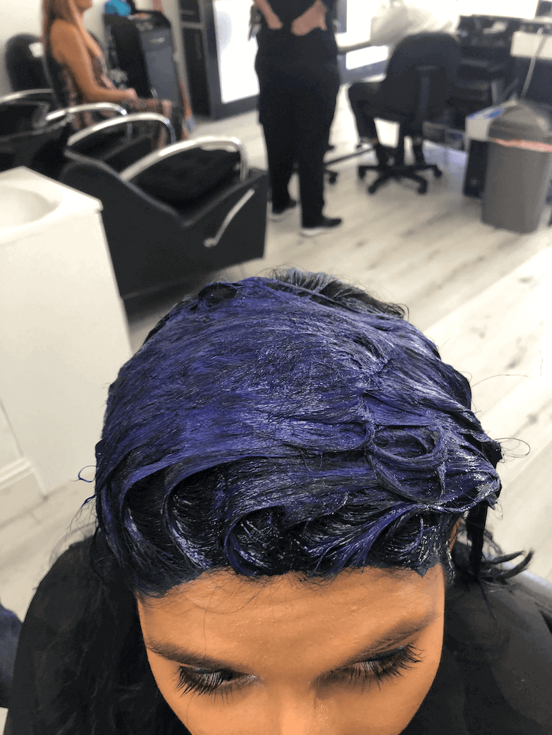 A girl with royal blue hair coloring in her hair at the salon.
